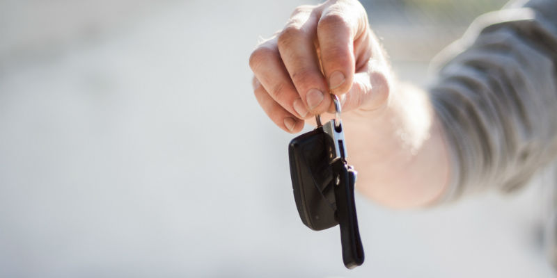 A car dealer holding out car keys