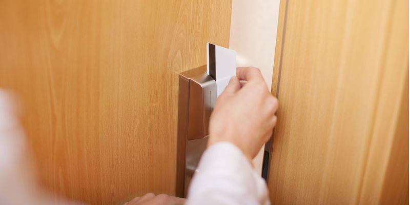 Person using key card to enter a room