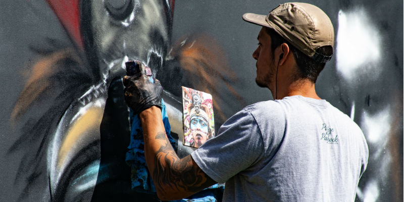 A vandal spray painting a wall